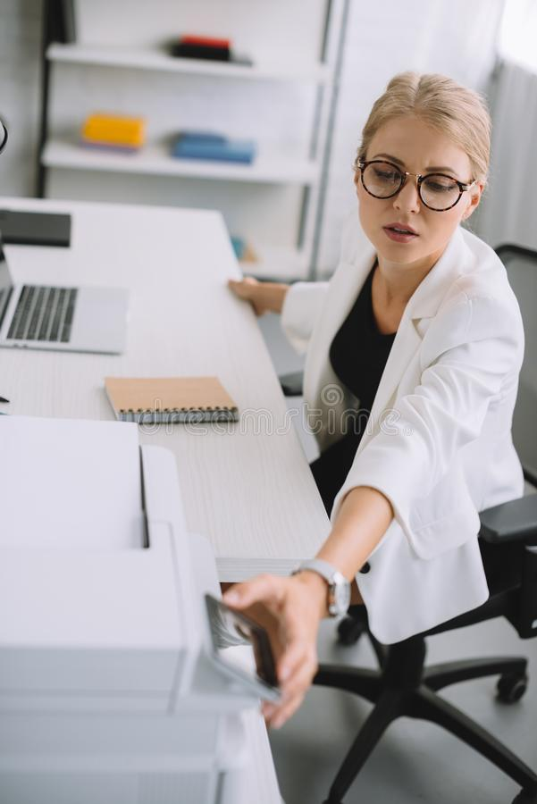 young businesswoman using printer while sitting at workplace with laptop stock photos