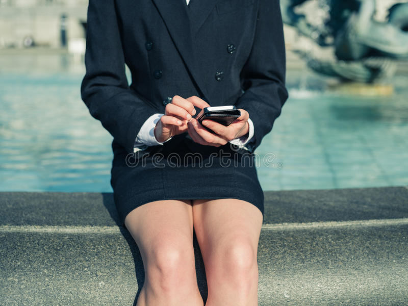 Young businesswoman using smart phone by fountain stock image