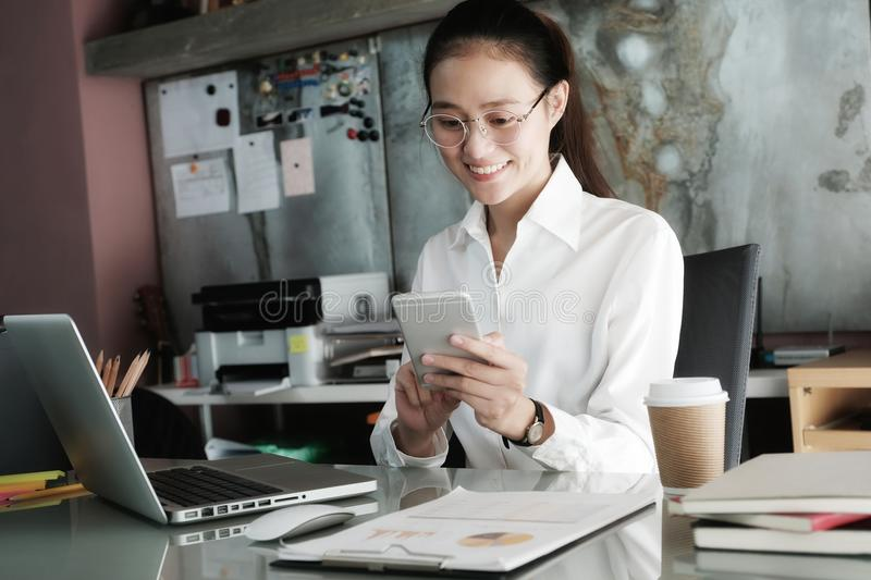 Young businesswoman using smart phone while working at her office desk background, business people and communication concept, off royalty free stock photo