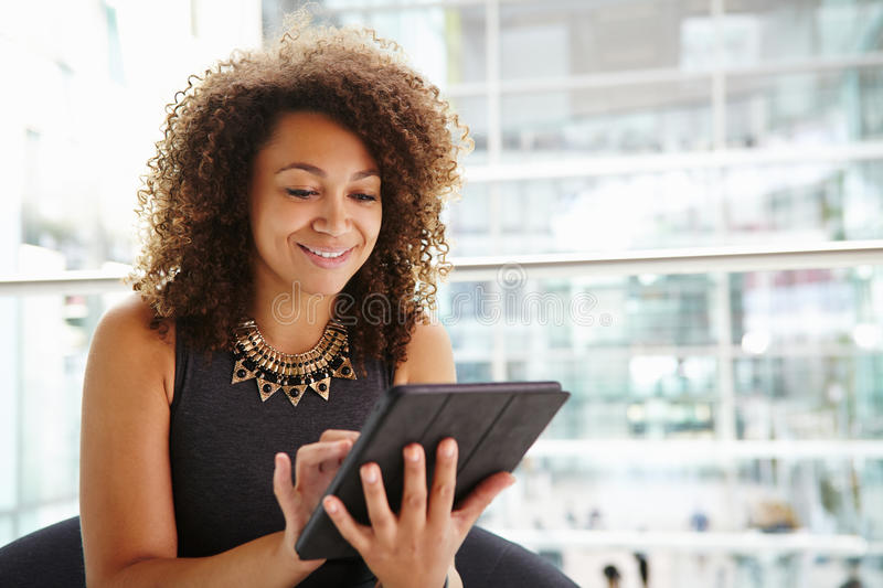 Young businesswoman using tablet computer in modern interior stock photography