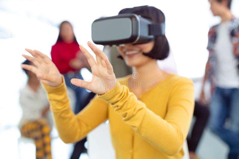 Young businesswoman using virtual reality headset in a modern office. Front view of happy young Asian businesswoman using virtual reality headset in a modern stock photo