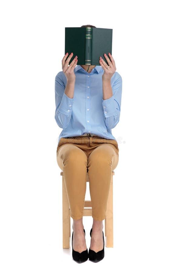 Young businesswoman hiding face behind book stock photos
