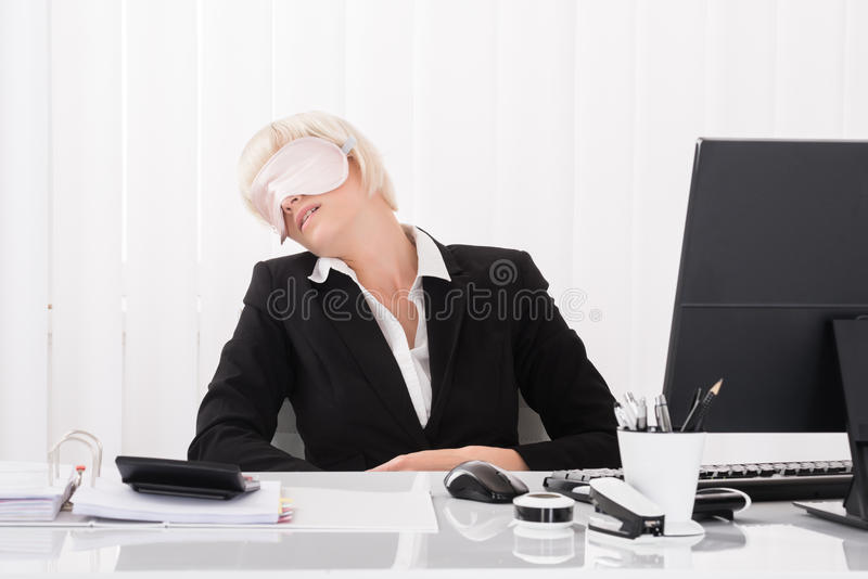 Businesswoman Wearing Eye Mask And Sleeping. Young Businesswoman Wearing Eye Mask And Sleeping In Office stock photo