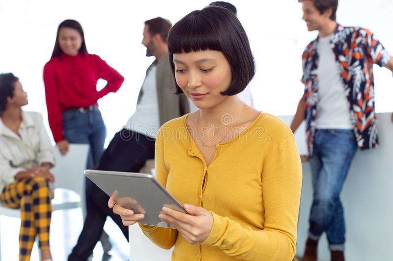 Young businesswoman working on digital tablet in a modern office. Front view of young Asian businesswoman working on digital tablet in a modern office stock images