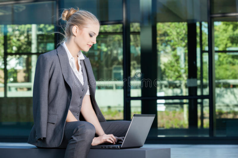 Young businesswoman working on laptop outdoors royalty free stock images