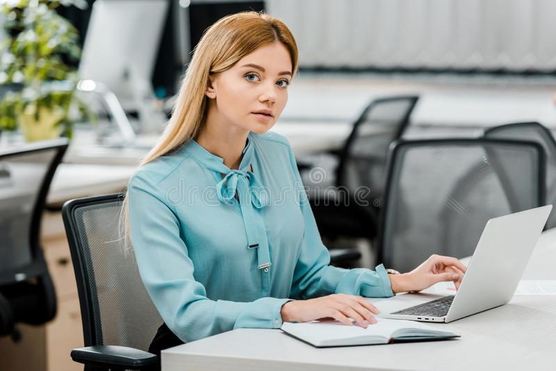 Young businesswoman at workplace with laptop and notebook. In office stock photography