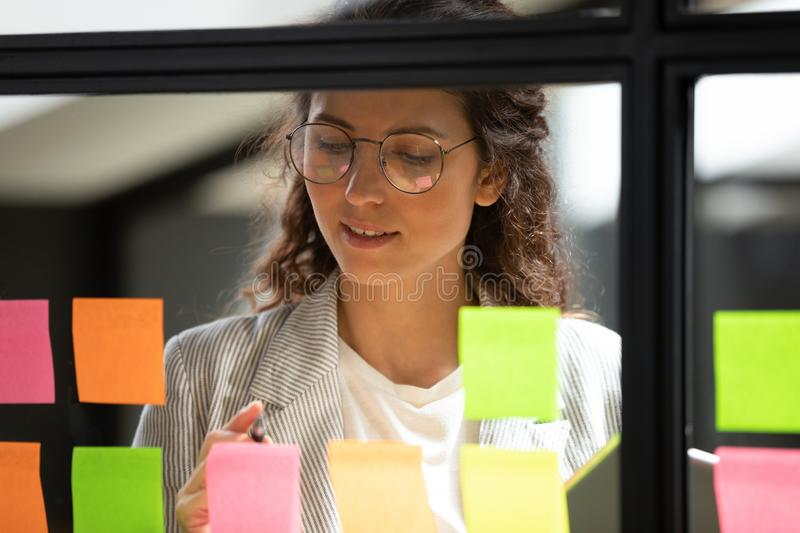 Young businesswoman write ideas on sticky notes on glass board royalty free stock photos