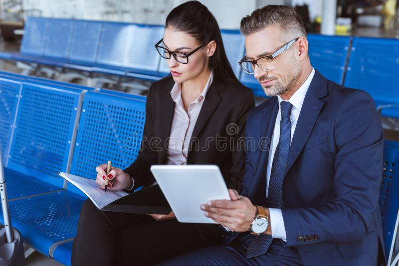 young businesswoman writing in notepad while businessman using digital tablet stock photos