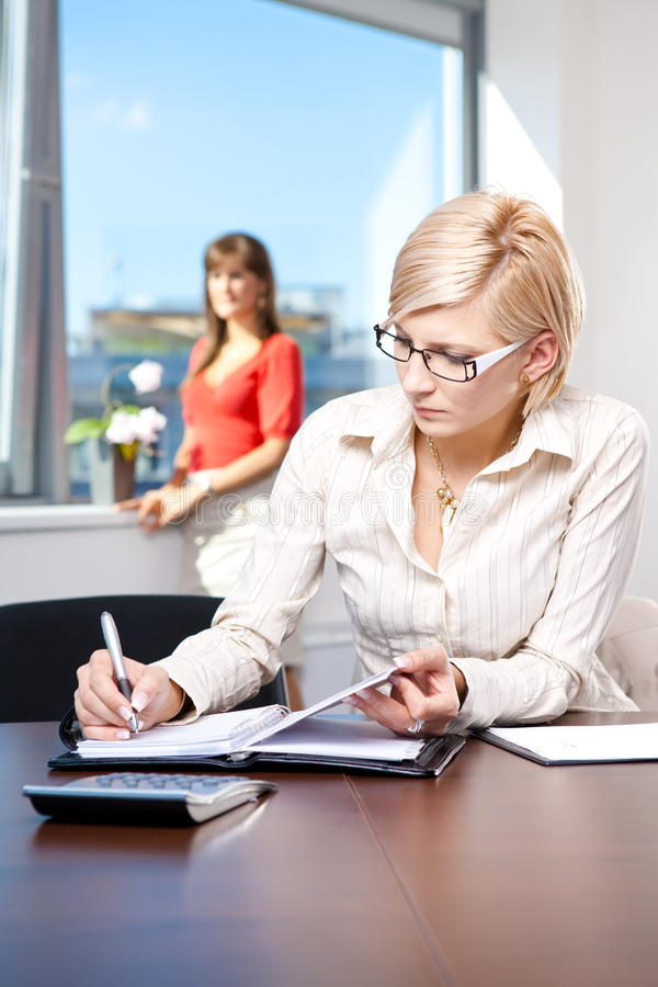 Young businesswoman writing notes stock image
