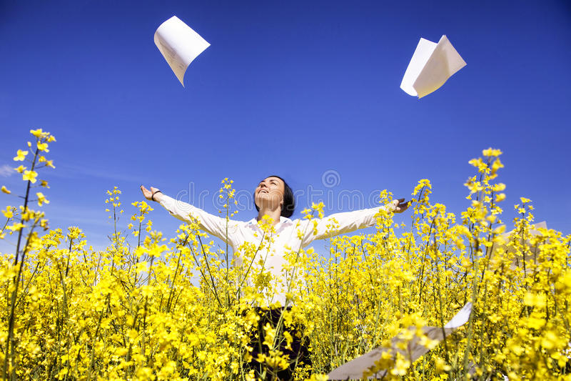 Young businesswoman among yellow flowers throw papers freedom stock images