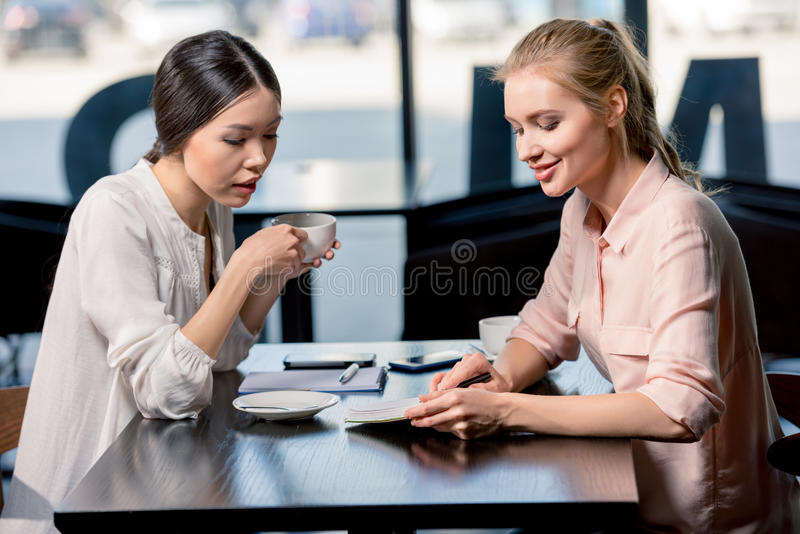 Young businesswomen looking at notebook and discussing project at coffee break stock image