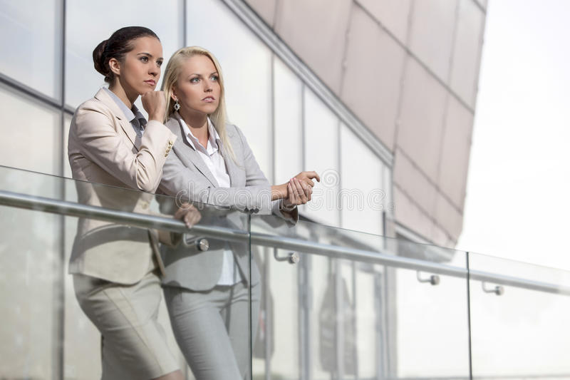 Download Young Businesswomen On Office Railing Looking Away Stock Image - Image: 33901485