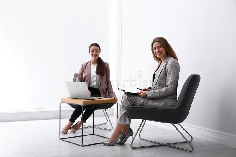 Young businesswomen sitting in armchairs at table. Indoors royalty free stock photography