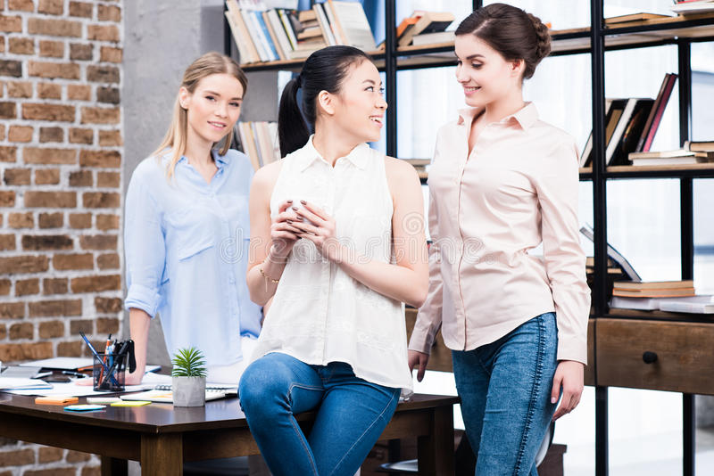 Young businesswomen smiling each other and drinking coffee at workplace stock photography