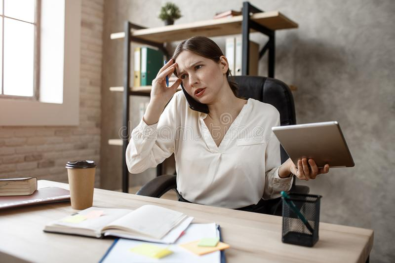 Young busineswoman has difficult talk on phone. She sit at table in room. Model hold tablet. Young busineswoman has difficult talk on phone. She sit at table in stock photography