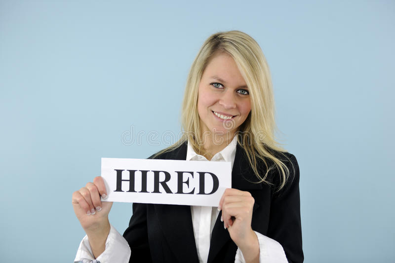 Young busineswoman holding hired sign. Happy young busineswoman holding hired sign royalty free stock photo