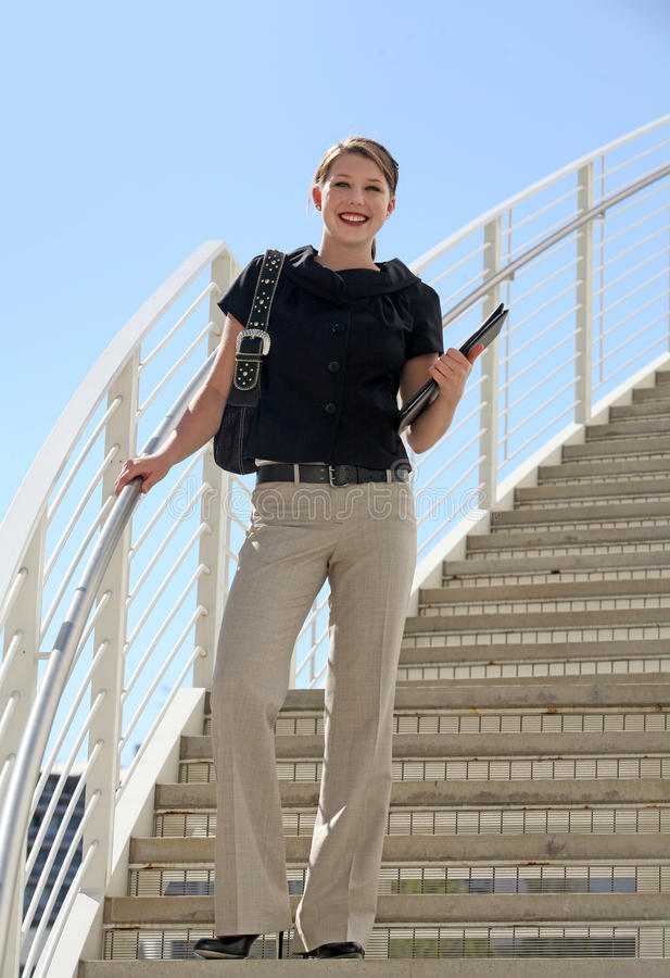 Young bussiness woman. A young business woman standing on the staircase royalty free stock image