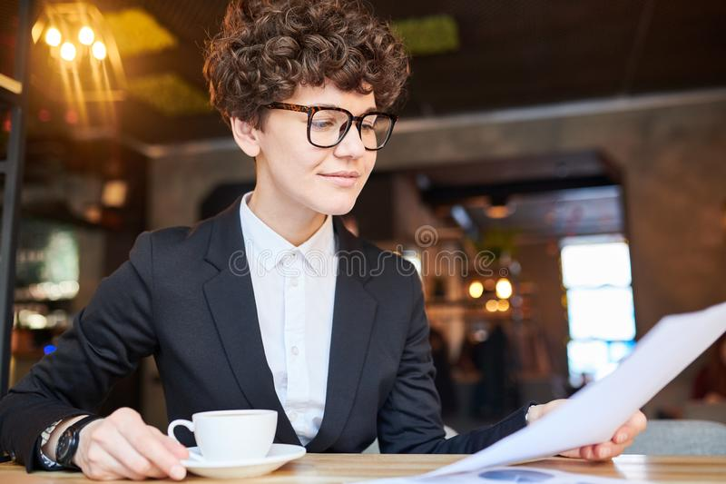 Agent reading contract. Young busy economist or trader having cup of tea in cafe and looking through financial document stock photography