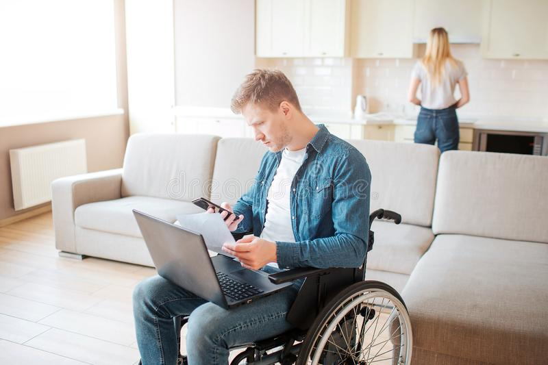 Young busy man with disability sitting on wheelchair. Hold laptop on knees. Young woman stand behind and cook. Daylight royalty free stock image
