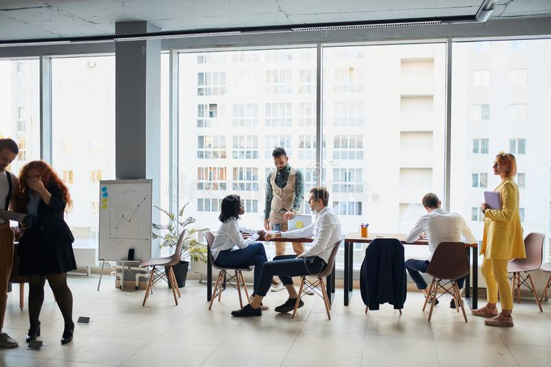 Young busy multiracial business people working together in coworking space. Busy multi-ethnic business people working together in coworking space, diverse royalty free stock photos