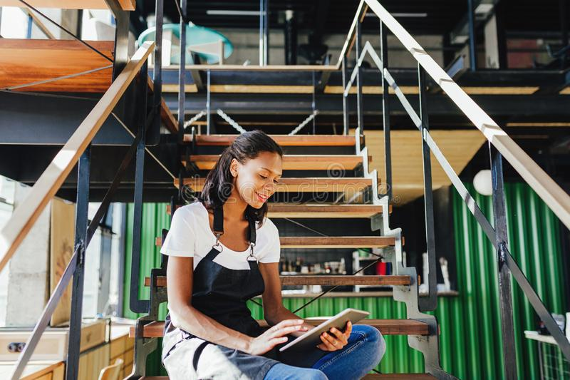 Young cafe owner sitting on staircase. royalty free stock photo