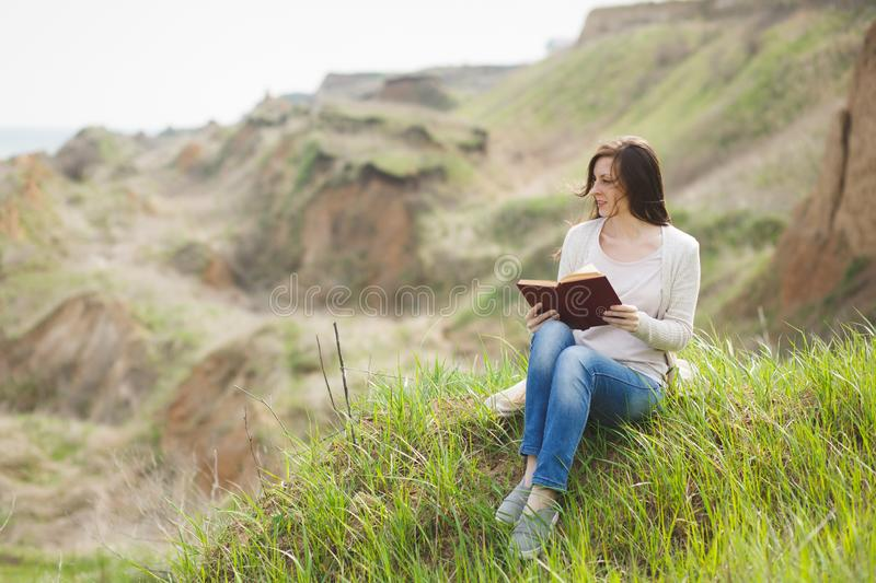 Young calm charming woman in light casual clothes sitting on grass studying reading book on green field background. Student learning, education. Beautiful stock photo