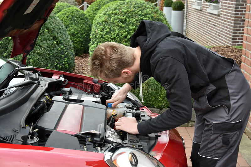 Young car mechanic at work. Young car mechanic checking functions of a car stock photo