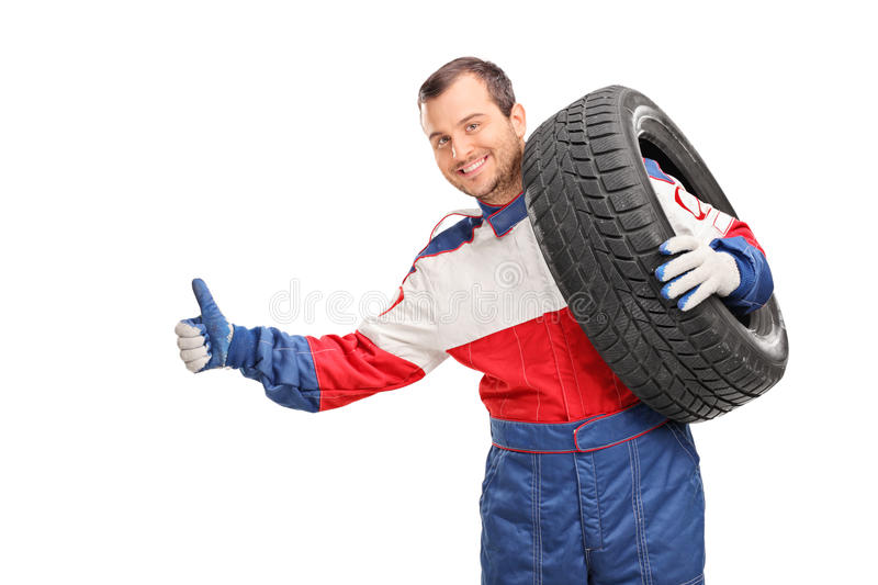 Young car racer hitchhiking. Young car racer carrying a tire on his shoulder and hitchhiking with his thumb isolated on white background royalty free stock images