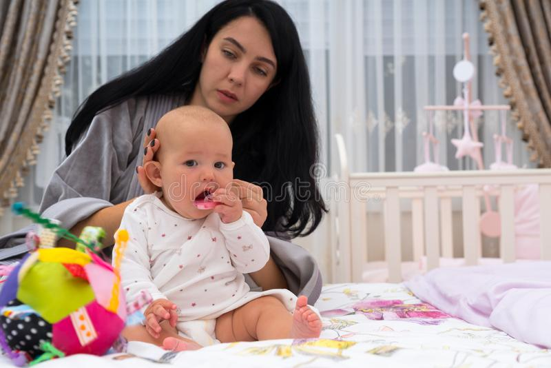 Young careful mother dressing baby in the morning. royalty free stock photography