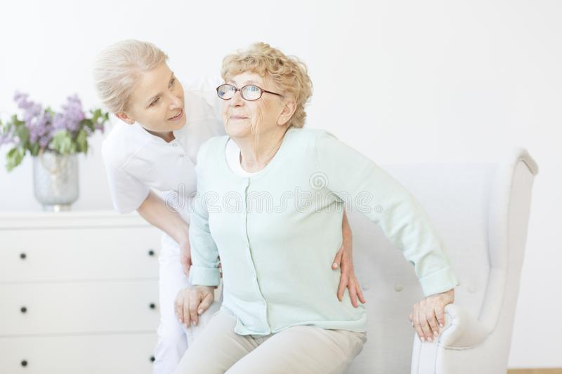 Young caregiver assisting smiling lady. Young caregiver assisting smiling elderly lady in glasses and mint sweater in nursing house stock photos