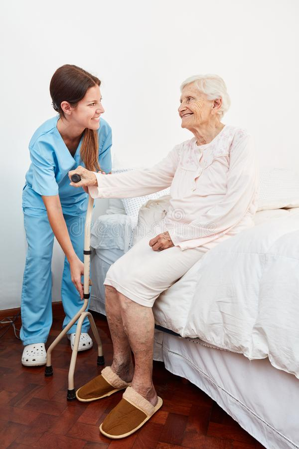 Young caregiver helps handicapped elderly woman stock photography