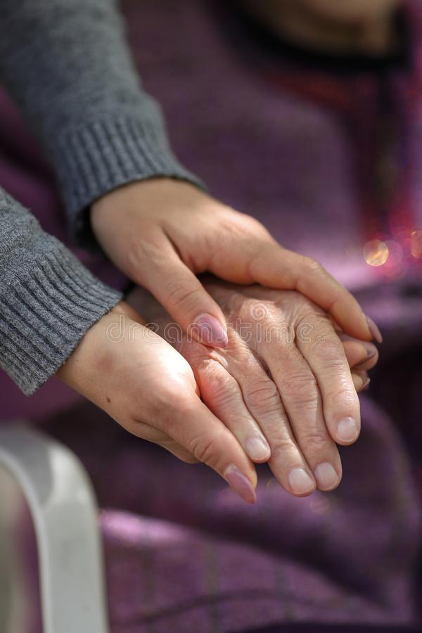 Young caregiver holding seniors hand. Elderly concept royalty free stock images