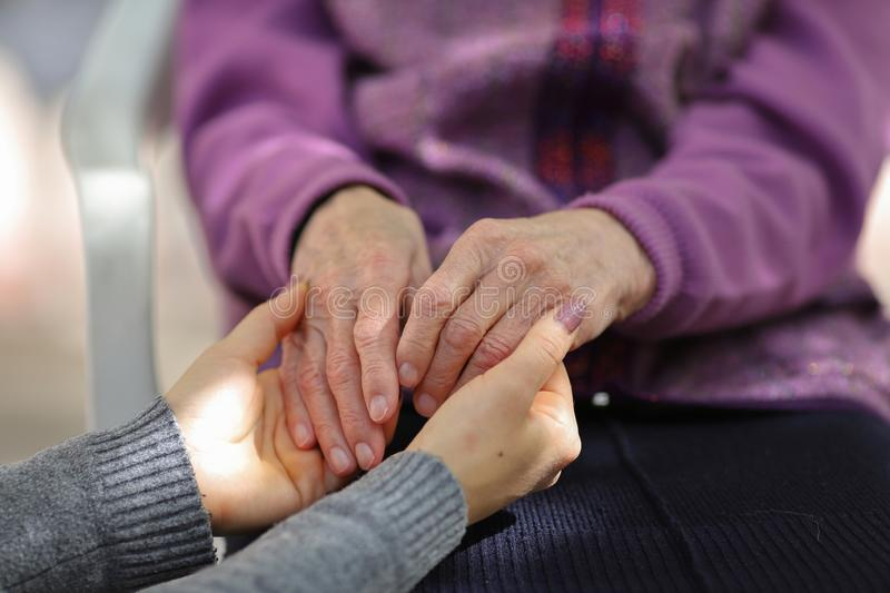 Young caregiver holding seniors hand. Elderly concept royalty free stock image