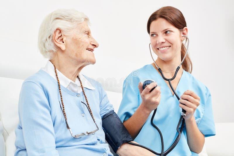 Nurse makes blood pressure measurement at senior citizen. Young caregiver makes a blood pressure measurement at senior women as a precaution at home stock images