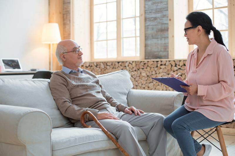 Young caregiver providing support for senior man. Social worker. Ambitious attractive caregiver using clipboard while wearing glasses and examining senior man royalty free stock image