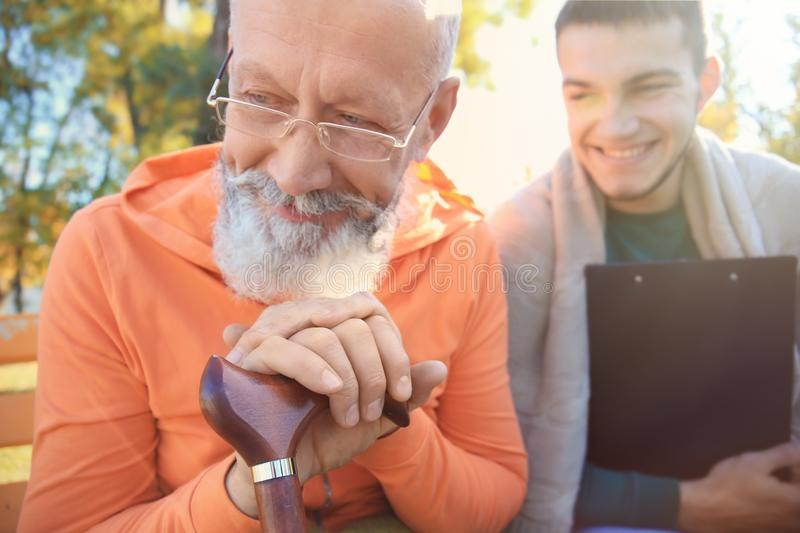Young caregiver sitting with senior man on bench. Young caregiver sitting with senior men on bench in park royalty free stock image