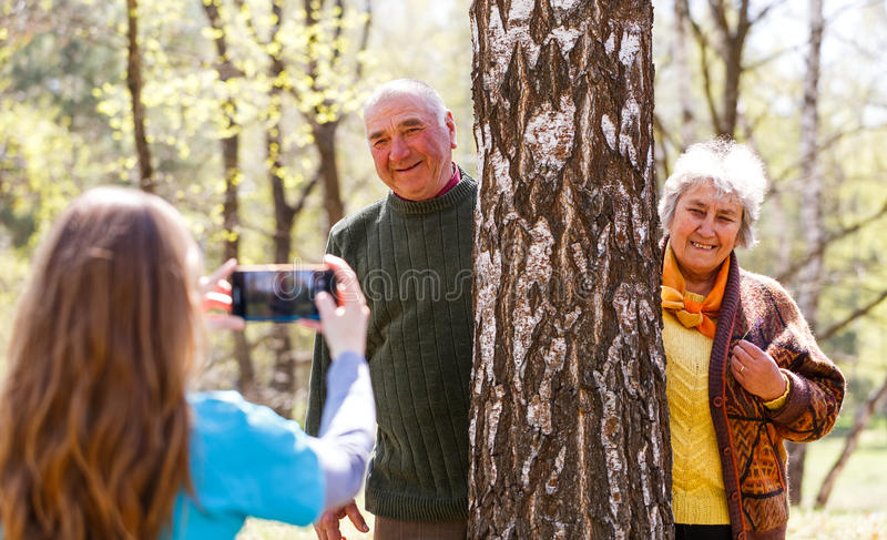 Young caregiver taking photo of elderly couple. Photo of young caregiver taking photo of elderly couple stock photography