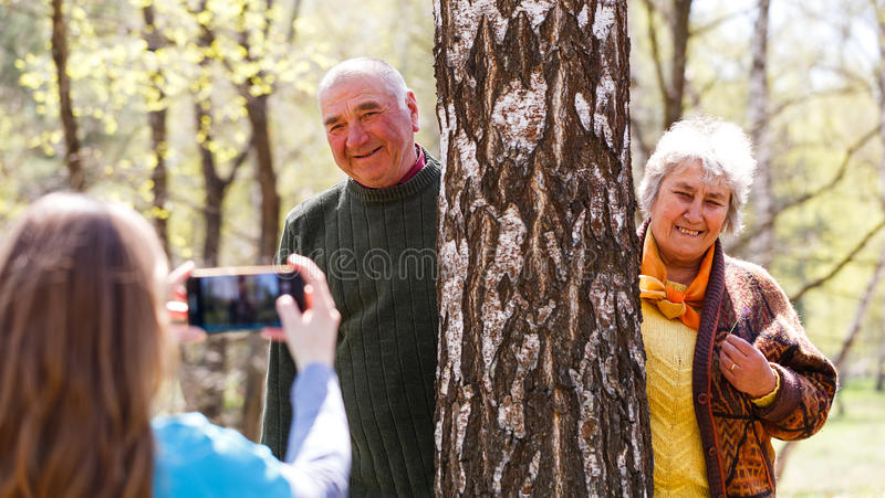 Young caregiver taking photo of elderly couple. Photo of young caregiver taking photo of elderly couple stock image