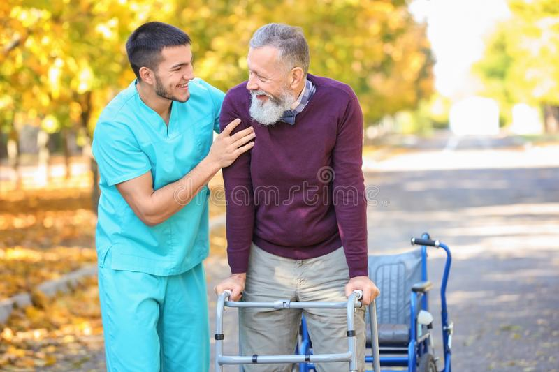 Young caregiver walking with senior man. Young caregiver walking with senior men in park royalty free stock photos
