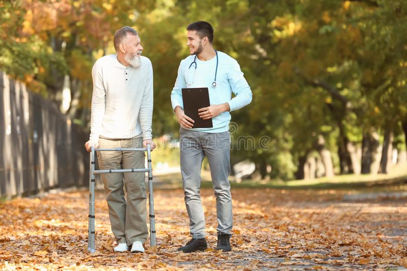 Young caregiver walking with senior man. Young caregiver walking with senior men in park stock photo