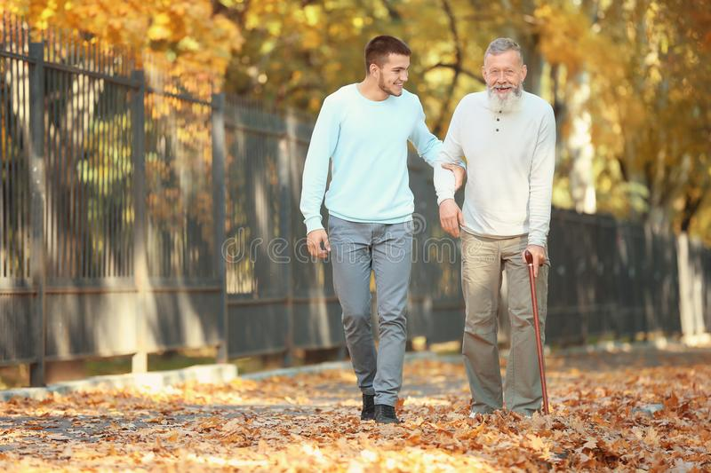 Young caregiver walking with senior man. Young caregiver walking with senior men in park stock photos