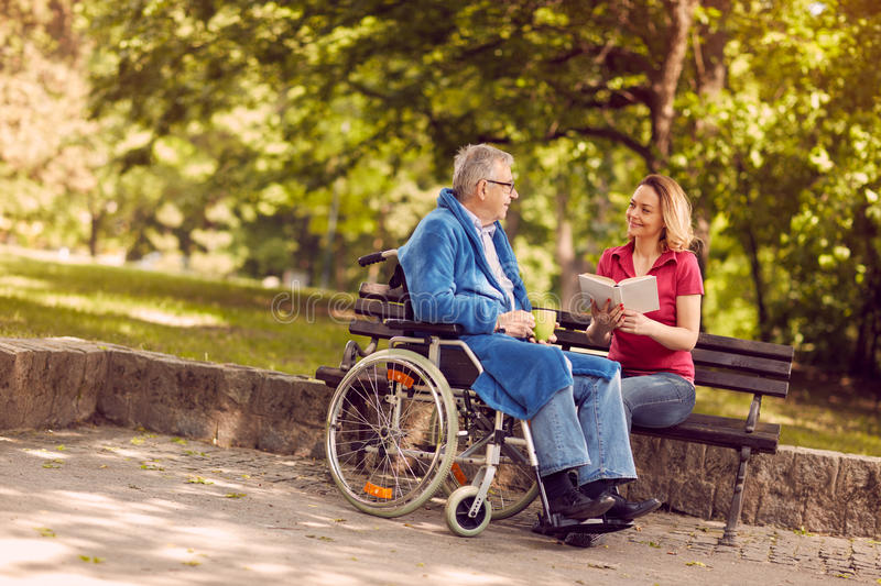 Young carer woman reading book outdoor disabled man in wheelchair. royalty free stock images