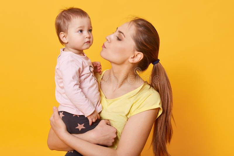 A young caring mother tries to calm down her crying daughter. A tear is going to run down cute baby`s cheek. A disappointed child. Looks concentrated on stock image