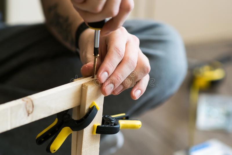 Young carpenter, handyman working with wood, using a screwdriver royalty free stock images