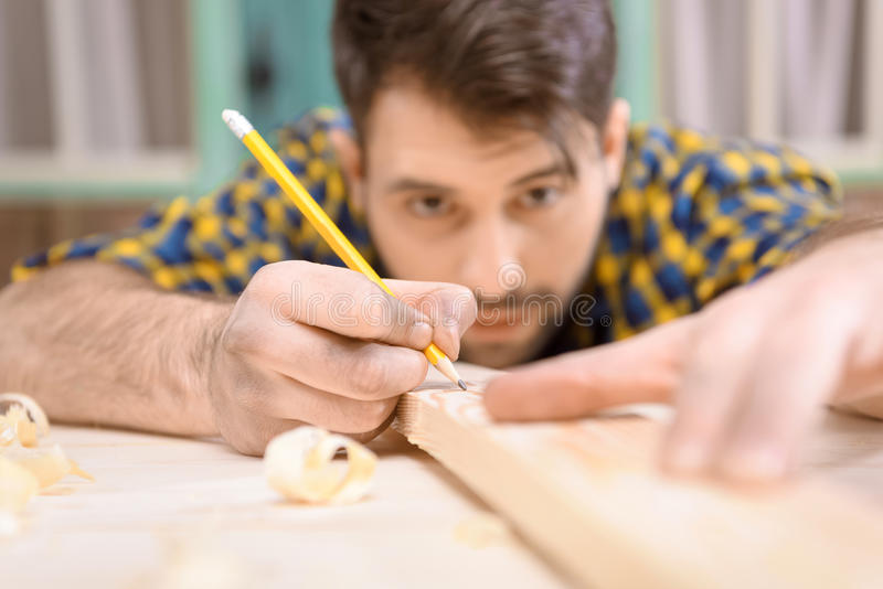 Young carpenter with pencil measuring and marking wooden plank royalty free stock photo
