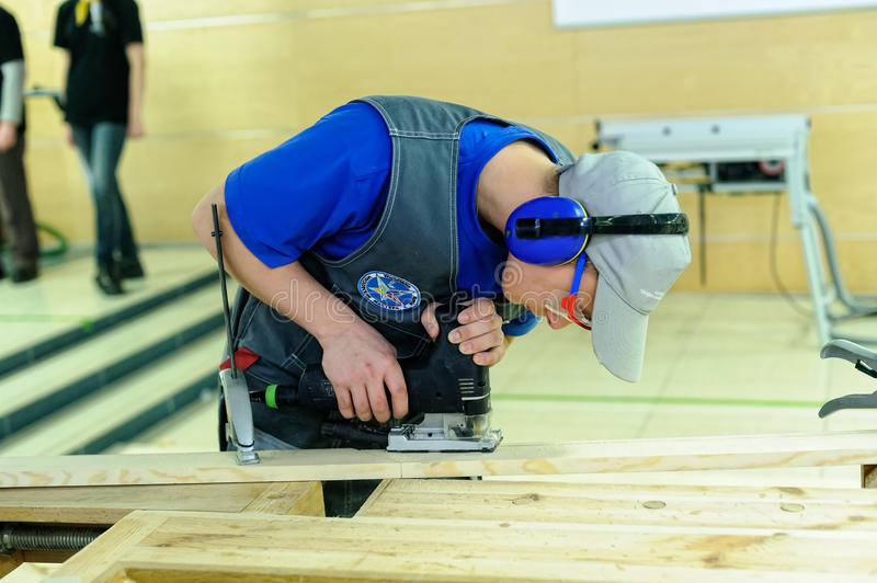Young carpenter performs task of competition. Tyumen, Russia - February 17. 2017: Open championship of professional skill among youth World skills Russia Tyumen stock images