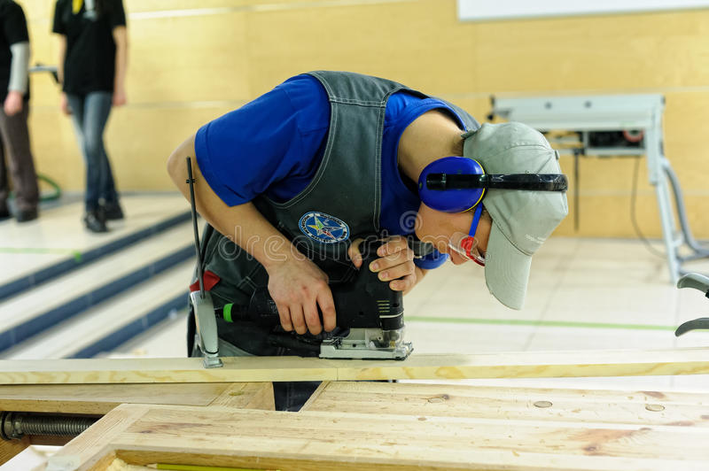 Young carpenter performs task of competition. Tyumen, Russia - February 17. 2017: Open championship of professional skill among youth World skills Russia Tyumen royalty free stock photo