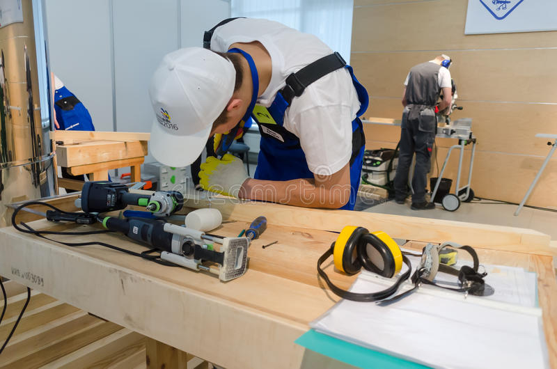 Young carpenter performs task of competition. Tyumen, Russia - March 24, 2016: Open championship of professional skill among youth. World skills Russia Tyumen stock image