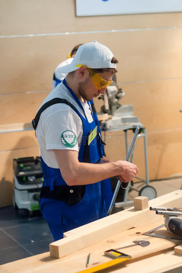Young carpenter performs task of competition. Tyumen, Russia - March 24, 2016: Open championship of professional skill among youth. World skills Russia Tyumen stock photo