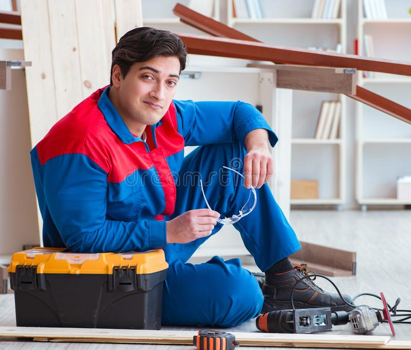 Young carpenter taking break from working with wooden planks stock image